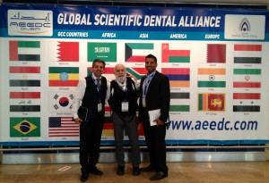 Dr. Jack Dillenberg and Dr. Tony Hashemian pose in front of the flags at the AEEDC in Dubai.