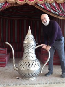 Dr. Jack Dillenberg poses by oversized ceremonial teapot in Dubai.