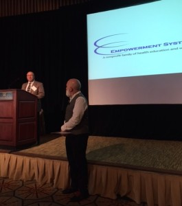 Dr. Jack Dillenberg presents an award to Elton Bordenaze from ATSU at the Empowerment Systems luncheon.