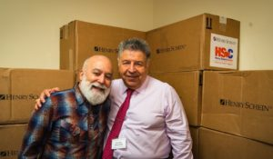 Dr. Jack and Henry Schein's Senior VP, Steve Kess, celebrate the arrival of Henry Schein Cares donation to ASDOH's outreach programs.