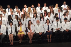 Students gather with Dean Dillenberg to take their D1 class picture during the White Coat Ceremony.